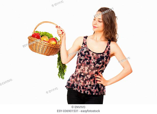 Gorgeous young brunette woman holding a basket of healthy food