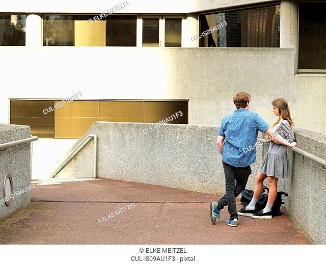 Young couple chatting on walkway, Melbourne, Victoria, Australia