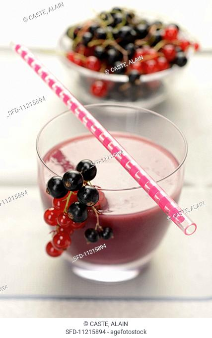 A smoothie made of black- and redcurrants, with fresh currants and a drinking straw