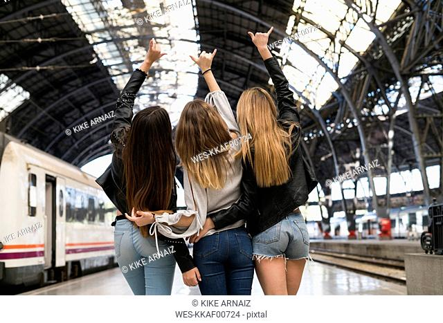 Back view of three young women standing arm in arm on platform