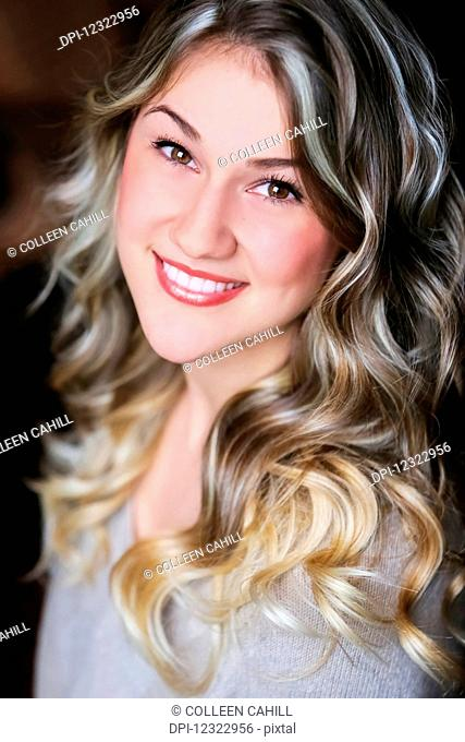 Portrait of a young woman with long blond curly hair; Oregon, United States of America