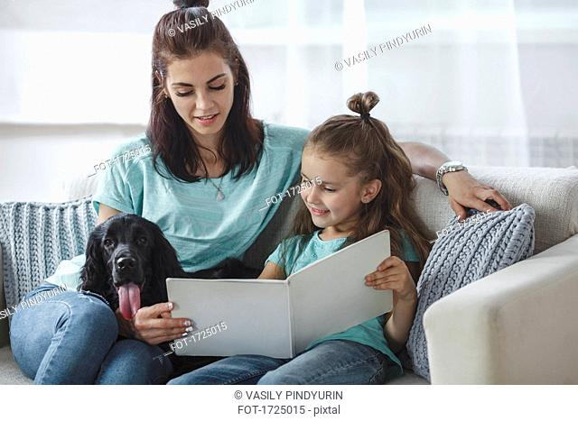 Girl reading book by mother and dog on sofa at home