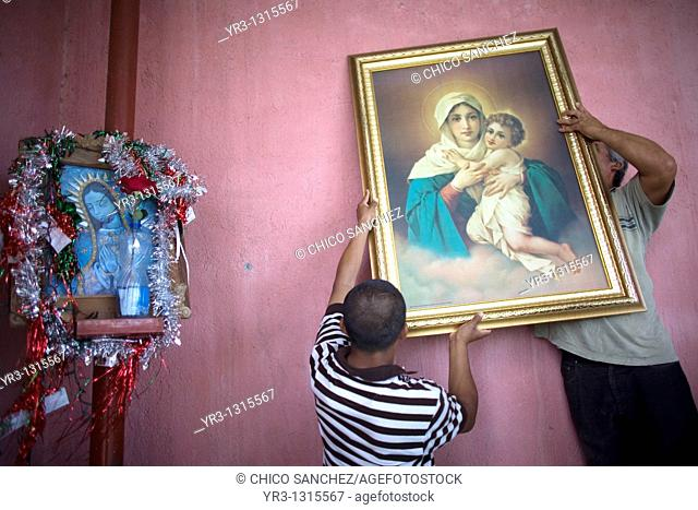 Central American migrants traveling across Mexico to work in the United States hang a picture of the Schöenstatt Virgin on the wall at the Catholic priest...