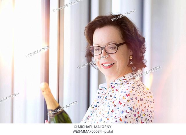 Smiling senior businesswoman holding bottle of champagne at the window