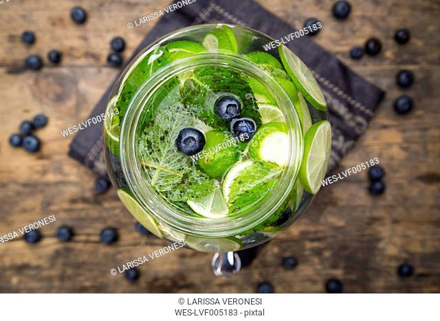 Glass of infused water with lime, blueberries and mint