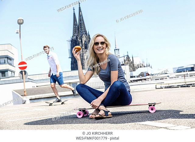 Germany, Cologne, portrait of young woman with bagel sitting on skateboard