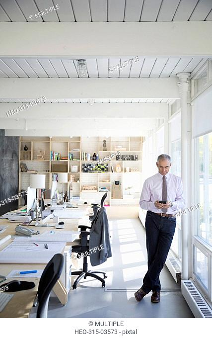 Male architect texting with cell phone in office
