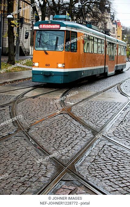 Tram in cobblestone street