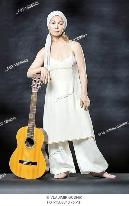 Portrait of confident woman standing with acoustic guitar against gray background