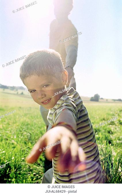 Portrait of a young boy reaching towards the camera