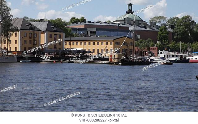 A sightseeing tour boat with tourists is passing Skeppsholmen in Stockholm, Sweden