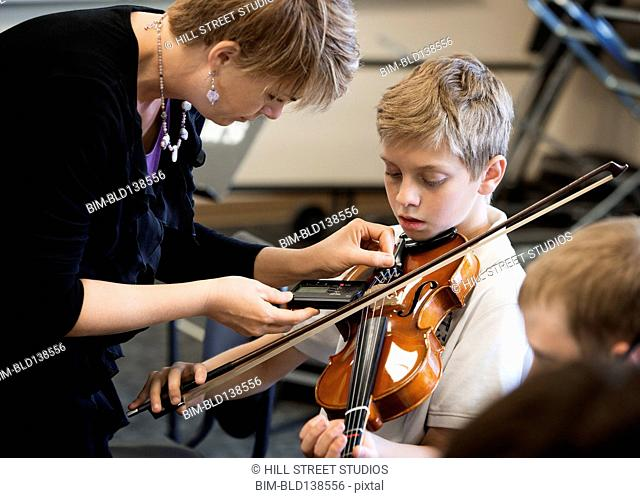 Caucasian teacher tuning students instrument in music class