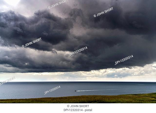 Ominous dark clouds over the ocean and a small boat traveling along the coastline; South Shields, Tyne and Wear, England