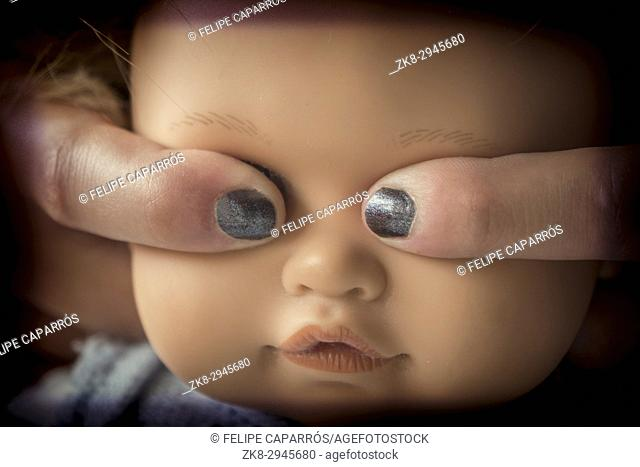 Fingers covering eyes of a doll