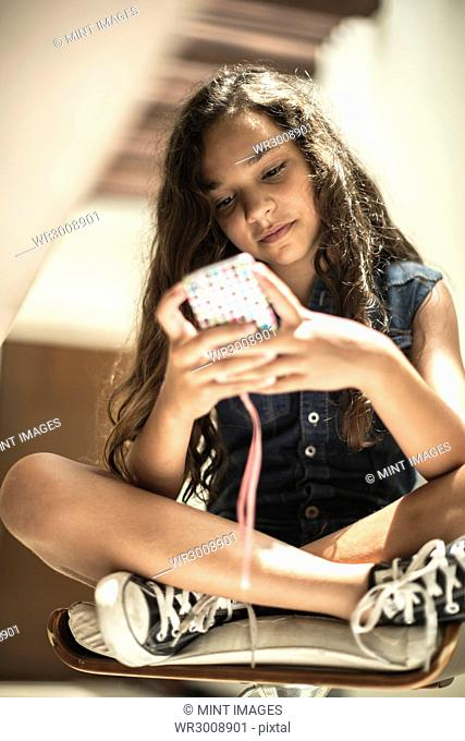 Low angle shot of a girl looking at a mobile phone screen