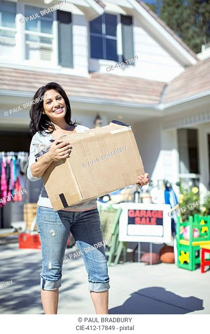 Portrait of smiling woman with box at garage sale
