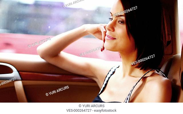 Cute young woman sitting in the passenger seat of a vehicle and smiling while looking out the window