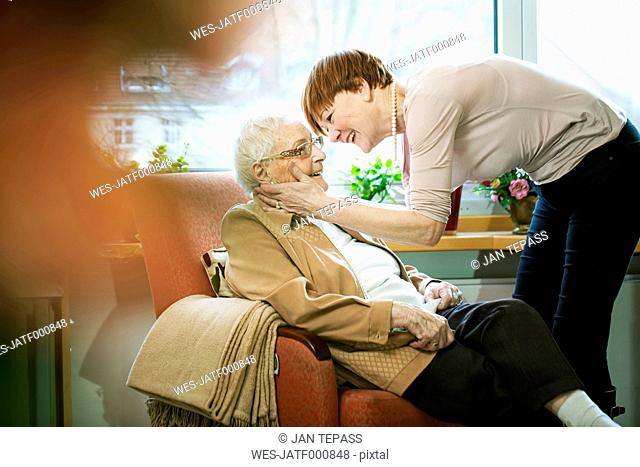 Adult daughter greeting her mother with Alzheimer's disease in her room at retirement home