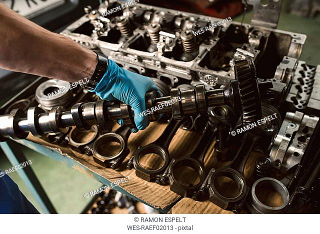 Close-up of mechanic holding the crankshaft of the engine of a car in a workshop