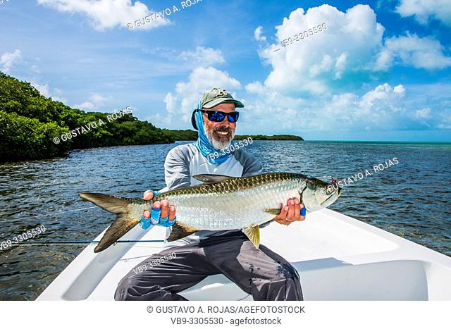 A fly fisherman with a small tarpon that caught with a fly rod on los roques - venezuela