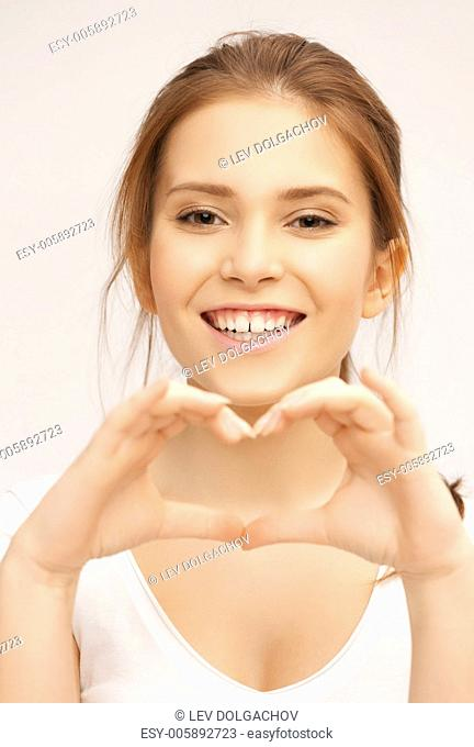 health, charity - woman in white shirt showing heart shape with hands