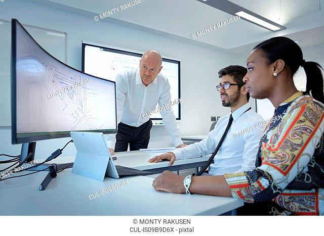 Teacher with apprentices studying screens in railway engineering facility
