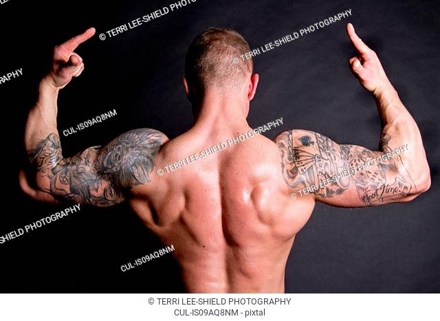 Young man showing rear double biceps