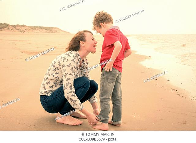 Young woman rolling up son's jeans on beach