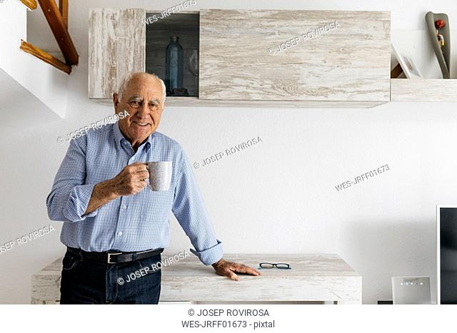Senior man having a coffee while relaxing at home, looking at camera
