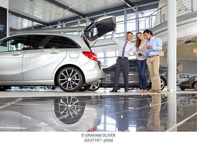 Salesman and couple with brochure looking into hatchback of car in car dealership showroom