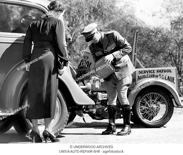 Los Angeles, California: c. 1930.A member of the service patrol of the Automobile Club of Southern California provides help to a broken down motorist