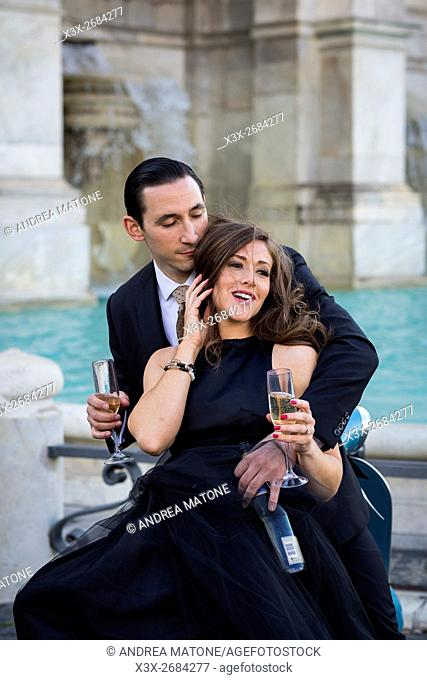 Couple toasting with a sparkling wine kissing while sitting on a vespa scooter. Janiculum water fountain. Rome, Italy