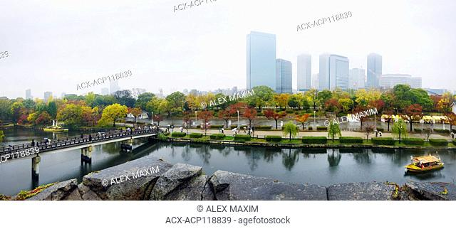 Osaka Castle Park canal with tourist boats and Gokurakubashi bridge panoramic misty autumn city scenery with Chuo-ku financial distric high-rise towers in the...