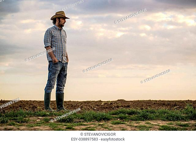 Portrait of Adult Male Farmer Standing on Fertile Agricultural Farm Land Soil,Looking into Distance