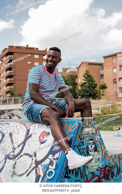 Young man in skatepark sitting on wall, laughing
