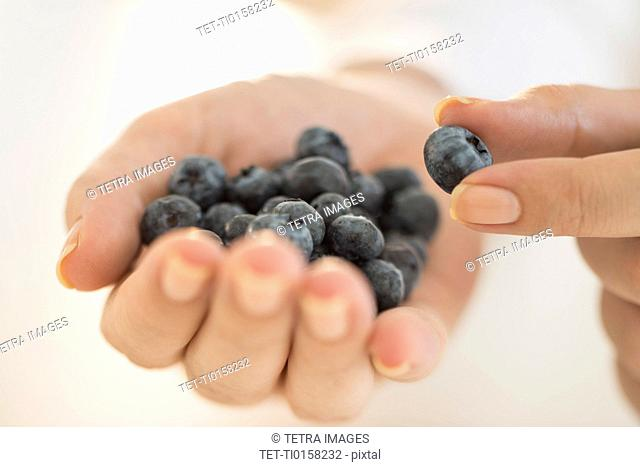 Blueberries on woman's hand