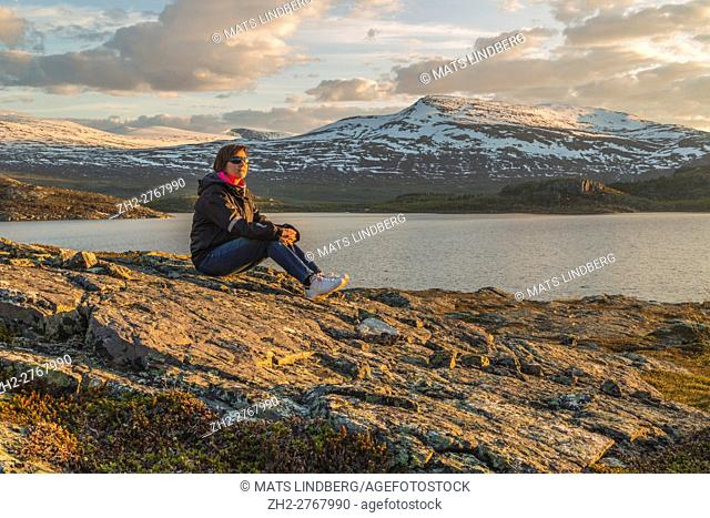 Woman with sunglasses and sneakers, sitting on a rock at sunset with mountains with snow and a lake in the background, Stora sjöfallets national park, Gällivare