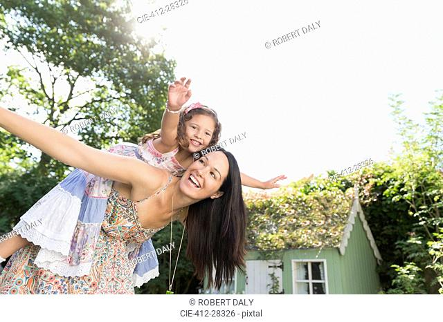 Carefree mother piggybacking daughter with arms outstretched in backyard