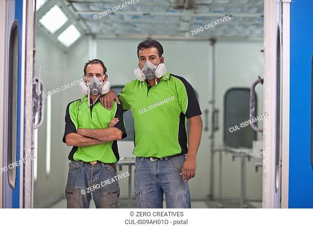 Portrait of carpenters in spray painting workshop doorway
