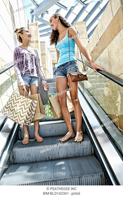 Mixed race teenage girls on escalator at shopping mall