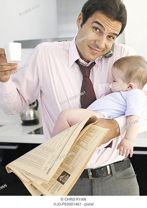 Father holding baby daughter while talking on phone in kitchen