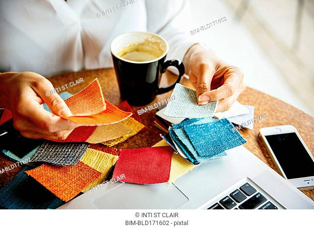 Mixed race designer examining fabric swatches