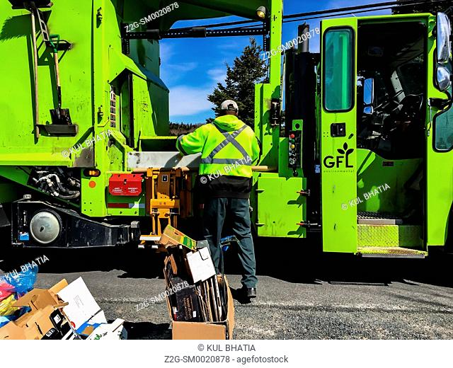 Recycling: A garbage man dressed in green loads recyclables into a green coloured truck, Halifax, Nova Scotia, Canada