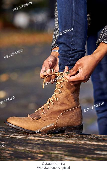 Hands of woman tying boot