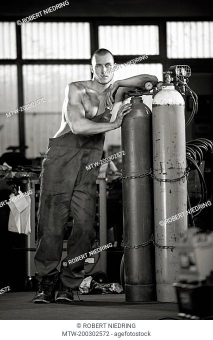 Young muscular man workshop oxyacetylene bottles