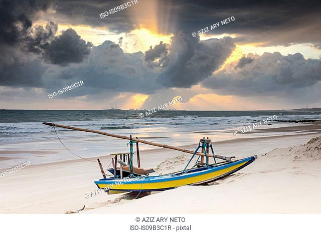 Beached fishing boat and dramatic sky at sunset, Taiba, Ceara, Brazil