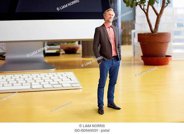 Mature businessman standing on oversized desk