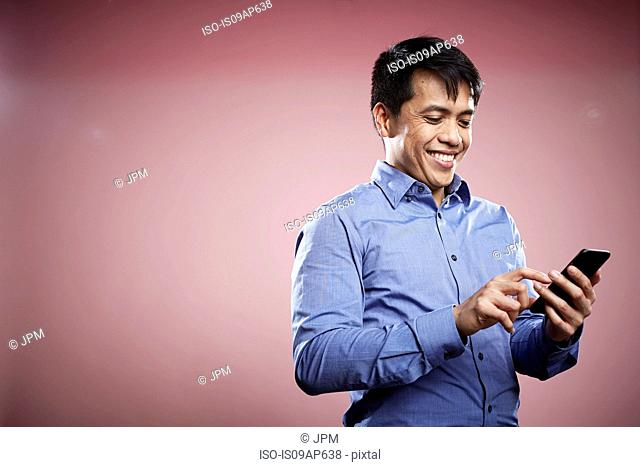 Portrait of mid adult man using smartphone