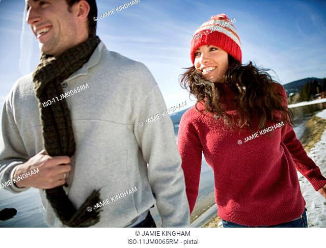 Couple running by snowy lake