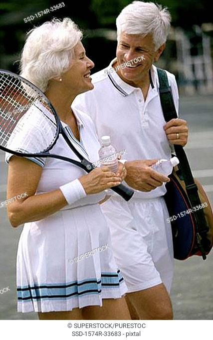 Senior couple together at a tennis court